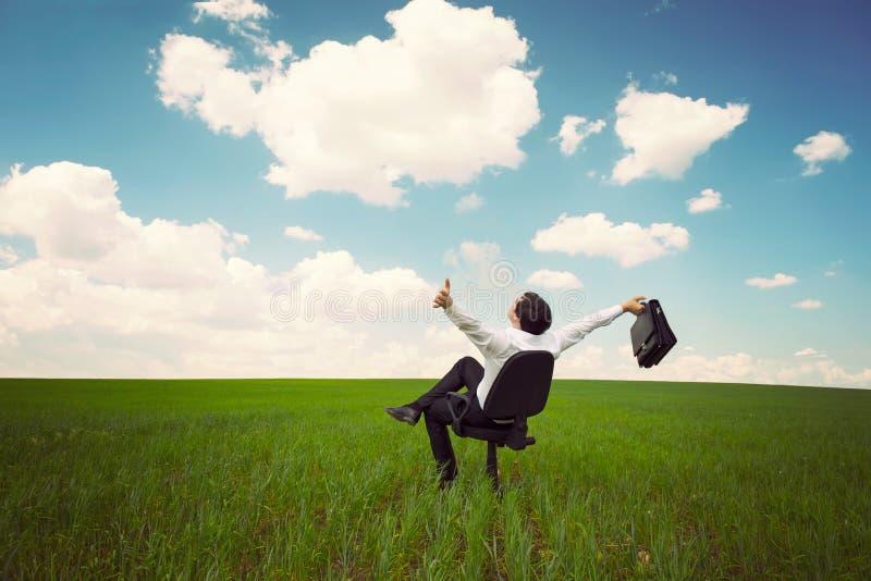 Uomo d'affari in un campo con un cielo blu che si siede su un ufficio chai immagini stock