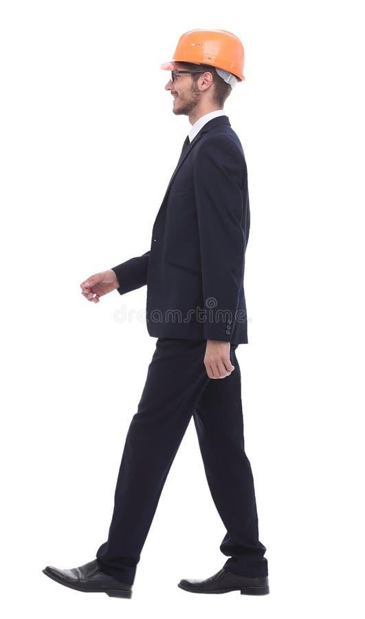 Uomo d'affari in un casco protettivo, facente un passo in avanti fotografie stock libere da diritti