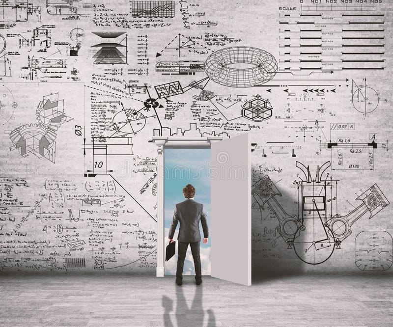 Uomo d'affari in un corridoio che prova a risolvere problema per la matematica immagine stock libera da diritti