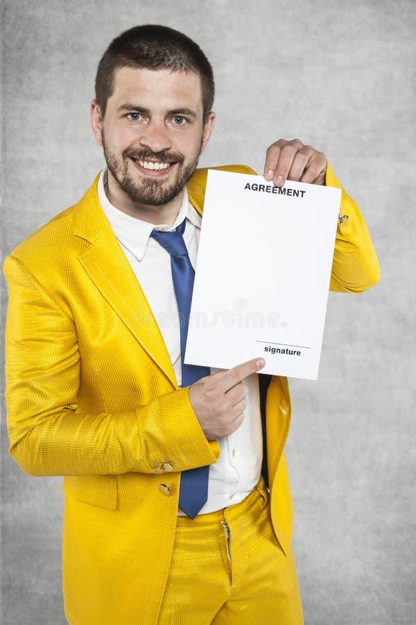 Uomo d'affari in un vestito che tiene un contratto dell'oro di lavoro fotografia stock