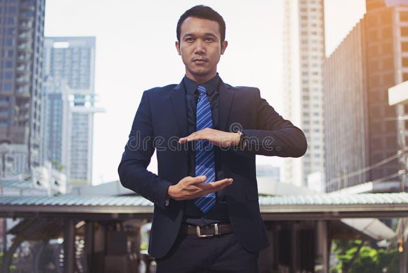 Uomo d'affari in un vestito e legame con la mano tesa per impleme fotografie stock
