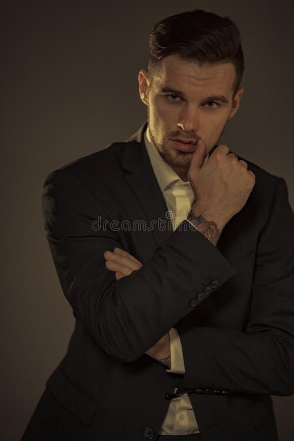 Uomo d'affari in un vestito e una camicia su fondo marrone immagini stock libere da diritti