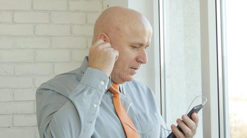 Uomo d'affari Use Headphones e Smartphone che accedono alla comunicazione online fotografia stock