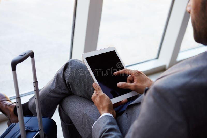 Uomo d'affari Using Digital Tablet nel salotto di partenza dell'aeroporto fotografia stock libera da diritti