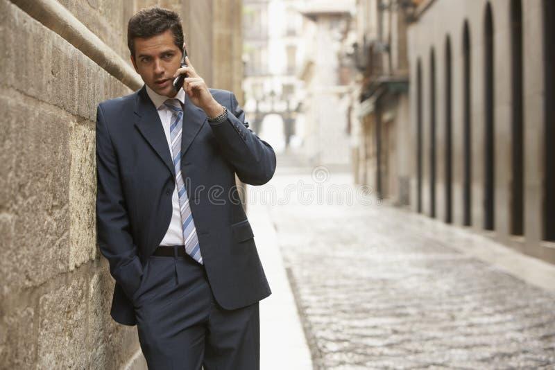 Uomo d'affari Using Mobile Phone in via immagine stock