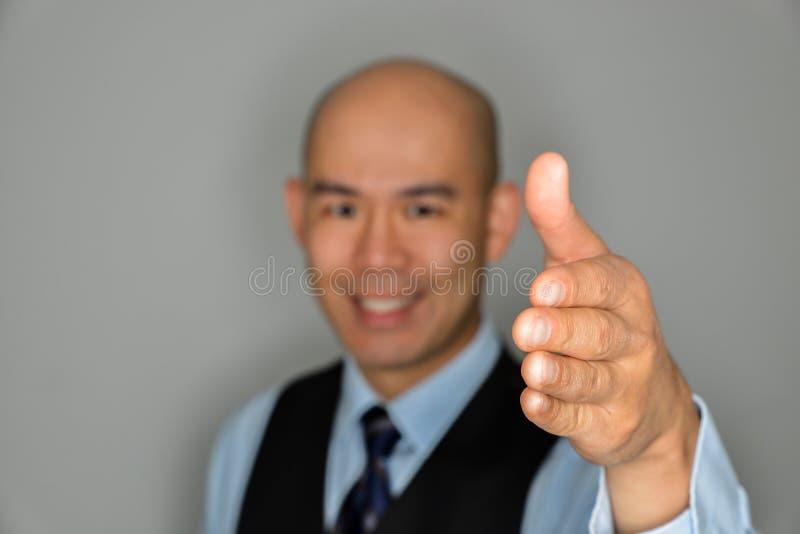 Uomo d'affari vago Offering Clear Handshake e sorriso immagini stock libere da diritti