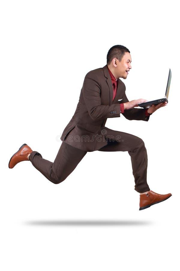 Uomo d'affari veloce Running mentre portando Lapto immagini stock