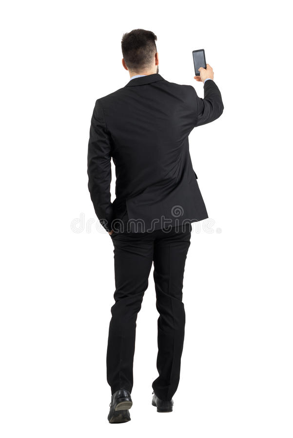 Uomo d'affari in vestito che cerca la retrovisione del buon segnale del telefono o che prende foto fotografia stock