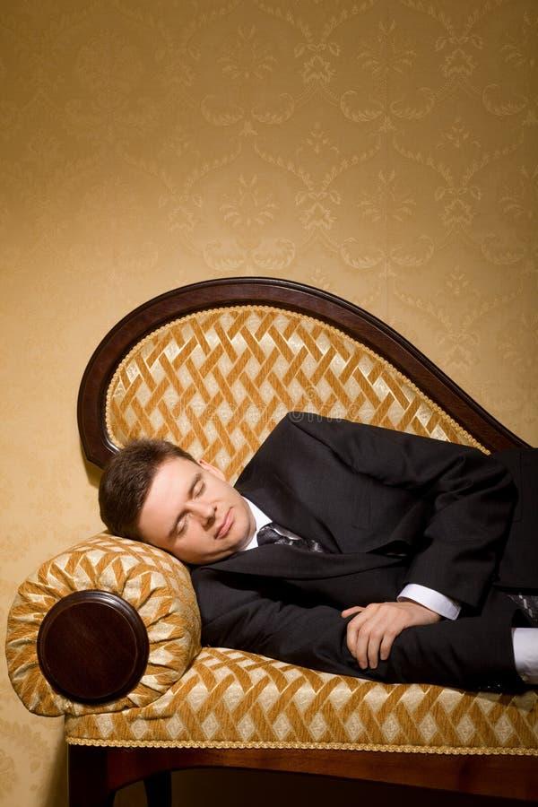 Uomo d'affari in vestito che dorme sul sofà nella sala fotografia stock libera da diritti