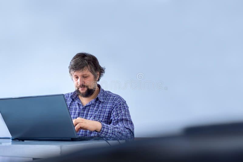 Uomo d'affari vestito con indifferenza Impiegato di concetto che scrive sul computer portatile Riuscito uomo d'affari che lavora  fotografie stock libere da diritti