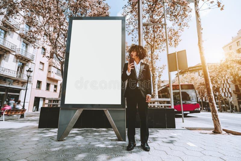 Uomo d'affari in vestito convenzionale vicino al modello urbano vuoto dell'insegna fotografia stock