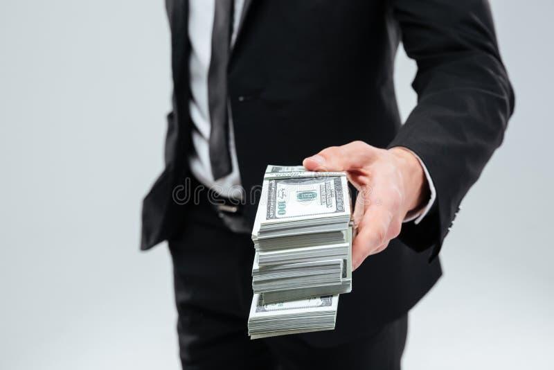 Uomo d'affari in vestito e legame che dà soldi voi fotografia stock