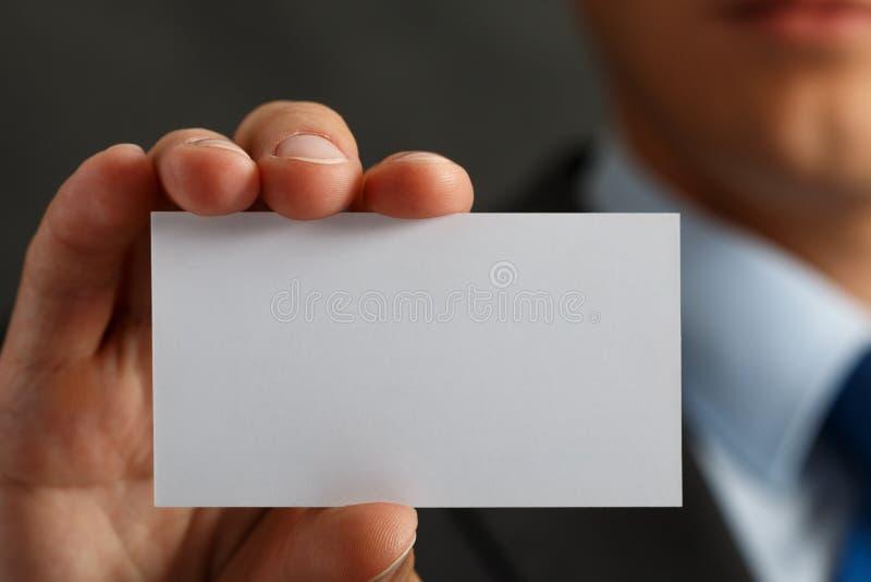 Uomo d'affari in vestito e mano che tiene la carta di chiamata in bianco fotografia stock
