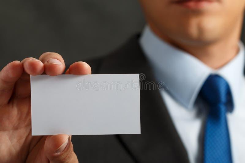 Uomo d'affari in vestito e mano che tiene la carta di chiamata in bianco immagine stock libera da diritti