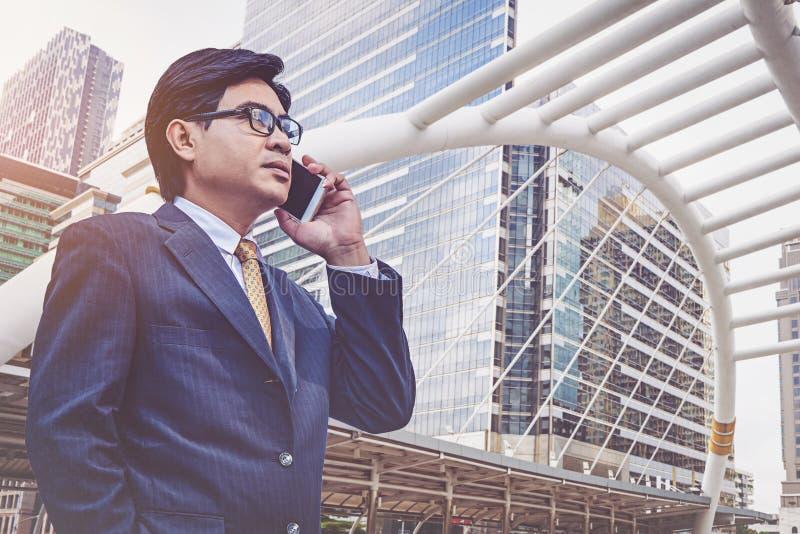 Uomo d'affari in vestito facendo uso dello smartphone alla città fotografia stock libera da diritti