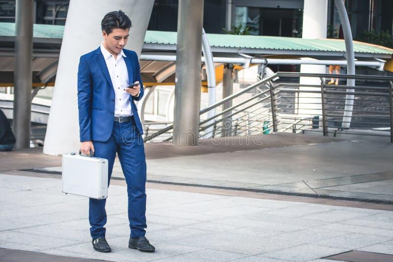 Uomo d'affari in vestito facendo uso dello smartphone alla città fotografia stock