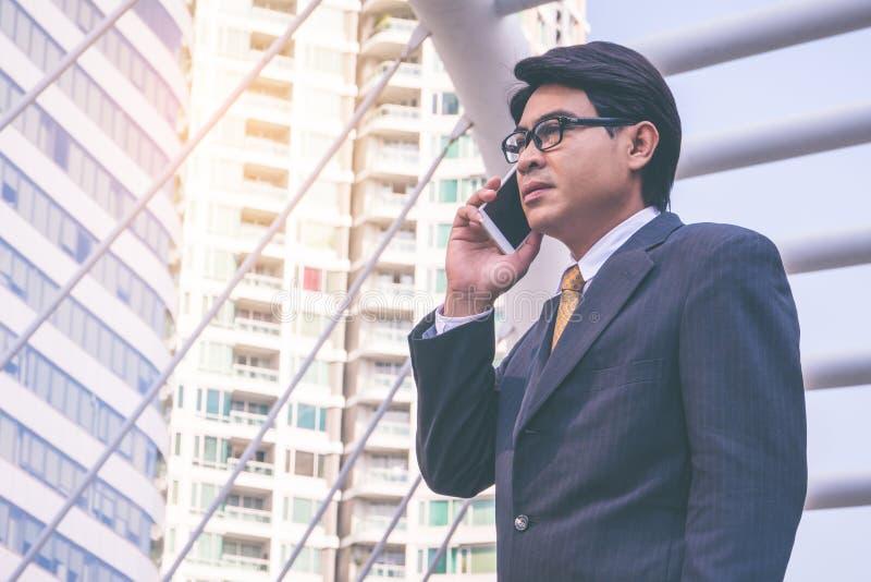 Uomo d'affari in vestito facendo uso dello smartphone alla città immagini stock libere da diritti