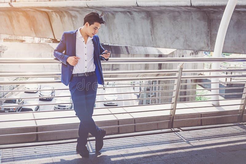 Uomo d'affari in vestito facendo uso dello smartphone alla città fotografie stock libere da diritti