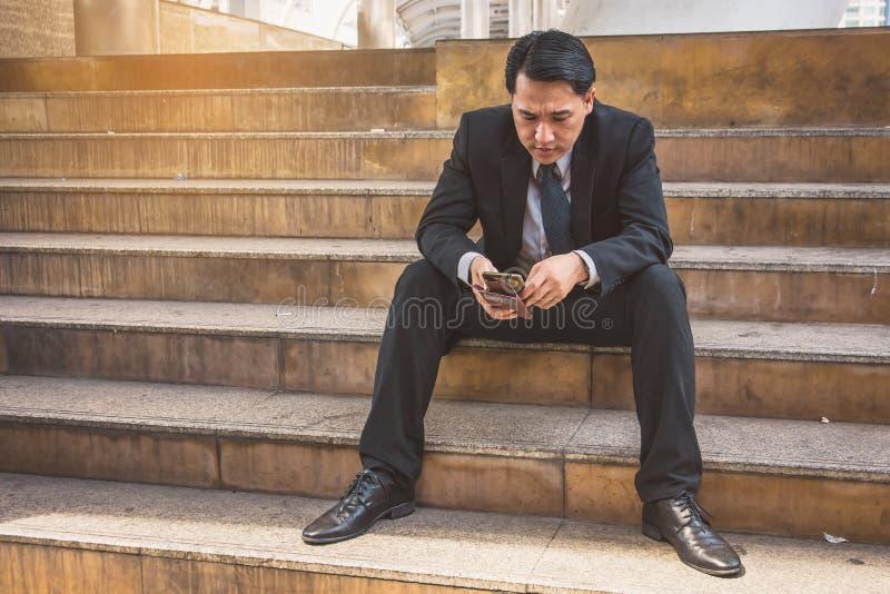 Uomo d'affari in vestito facendo uso dello smartphone alla citt? immagine stock libera da diritti