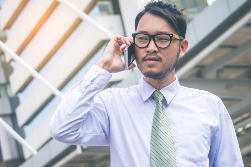 Uomo d'affari in vestito facendo uso dello smartphone alla citt? immagini stock libere da diritti