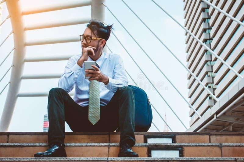 Uomo d'affari in vestito facendo uso dello smartphone alla citt? immagini stock