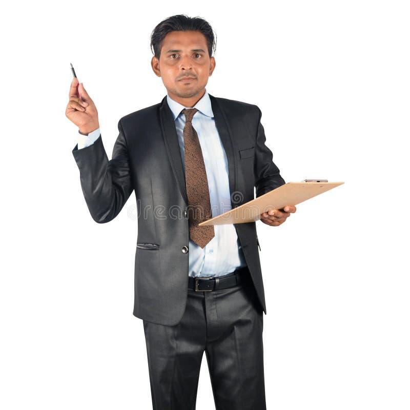 Uomo d'affari in vestito nero con la presentazione della lavagna per appunti e della penna fotografia stock libera da diritti