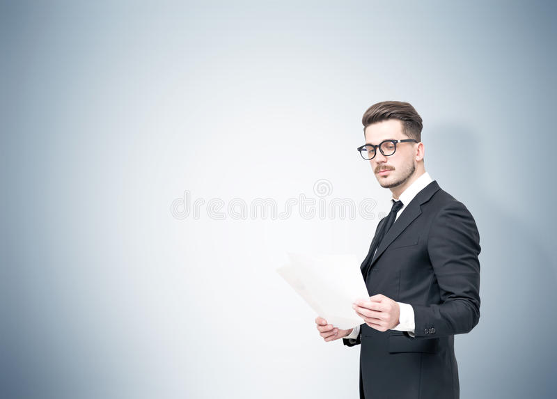 Uomo d'affari in vetri che legge i documenti, grigi immagine stock