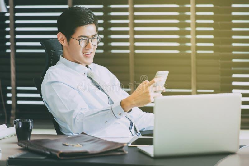 Uomo d'affari in vetri che si siedono alla scrivania con il computer portatile fotografie stock
