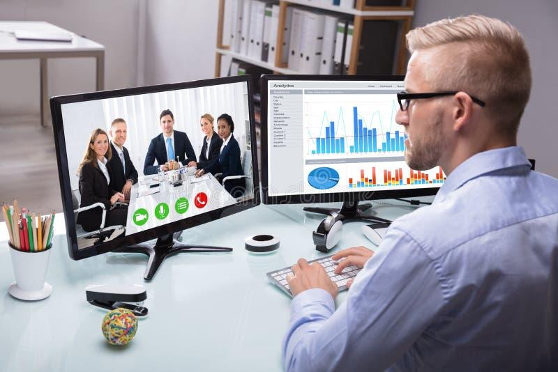 Uomo d'affari Video Conferencing With il suo collega immagine stock