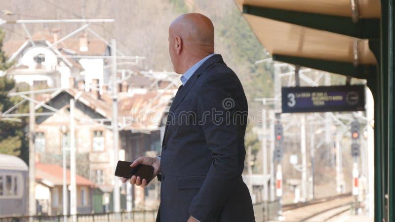 Uomo d'affari Waiting una riunione nella stazione ferroviaria immagini stock