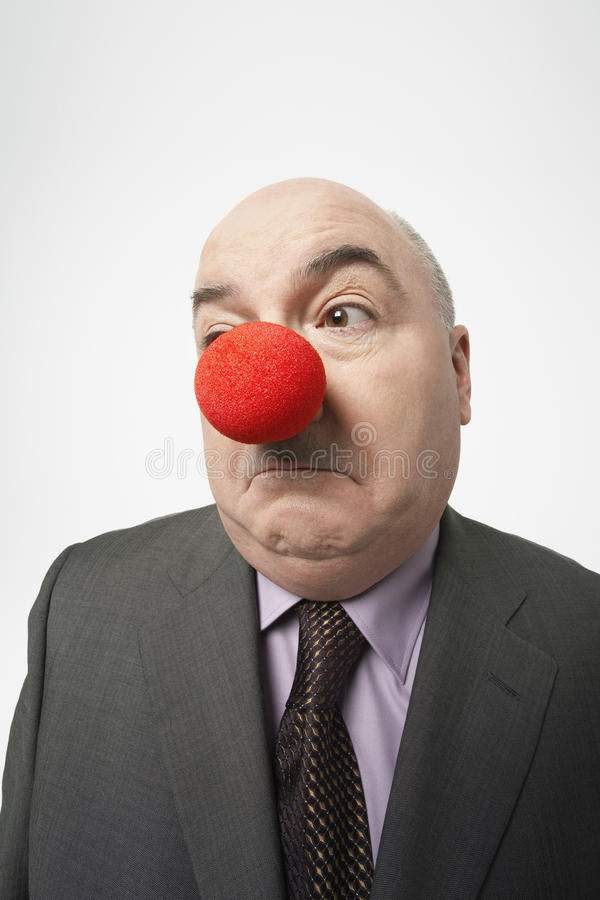 Uomo d'affari Wearing Clown Nose che aggrotta le sopracciglia fotografia stock libera da diritti