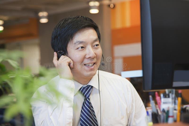 Uomo d'affari Wearing Headset nell'ufficio e nella conversazione fotografia stock