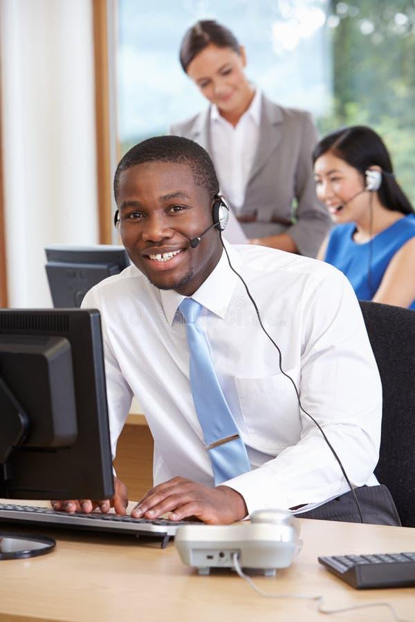 Uomo d'affari Wearing Headset Working in ufficio occupato immagine stock