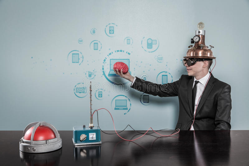 Uomo d'affari Wearing Helmet Holding Brain By Connecting Laptops Text fotografie stock