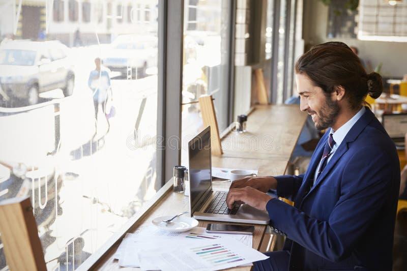 Uomo d'affari By Window Working sul computer portatile in caffetteria fotografia stock