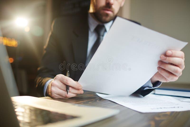 Uomo d'affari Working con documentazione allo scrittorio fotografia stock libera da diritti