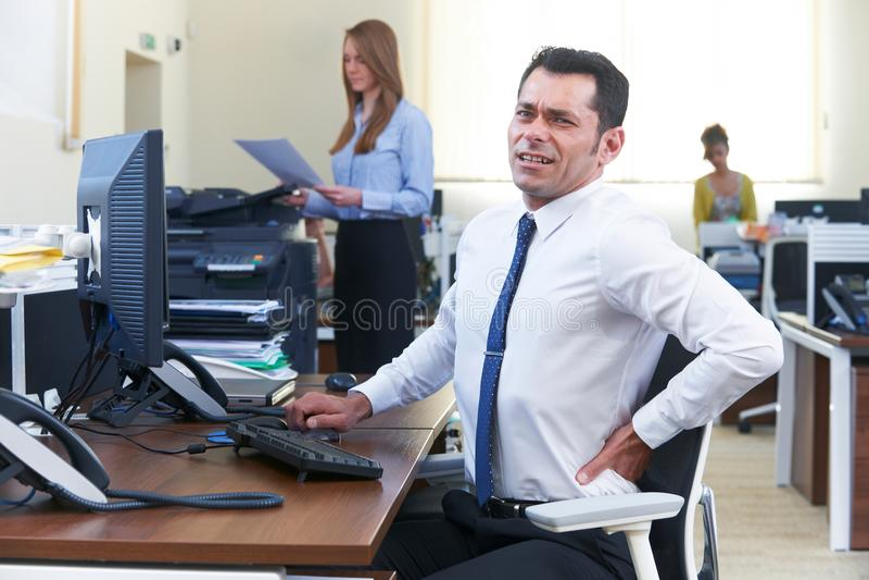 Uomo d'affari Working At Desk che soffre dal mal di schiena fotografie stock libere da diritti
