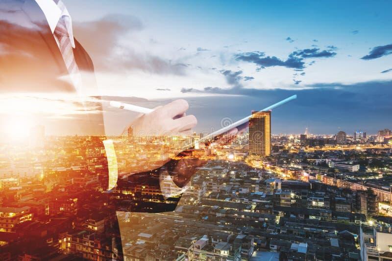 Uomo d'affari Working di doppia esposizione sulla compressa di Digital all'aperto e fondo di vista della città immagini stock libere da diritti