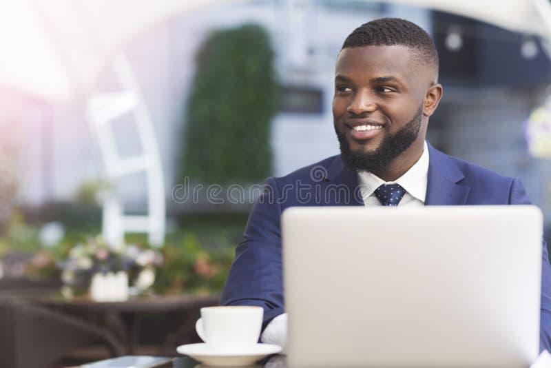 Uomo d'affari Working On Laptop di afro che mangia caffè in caffè all'aperto fotografia stock libera da diritti