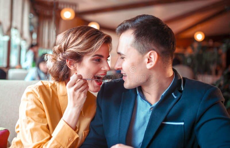 Uomo d'alimentazione della giovane donna con un cucchiaio immagini stock