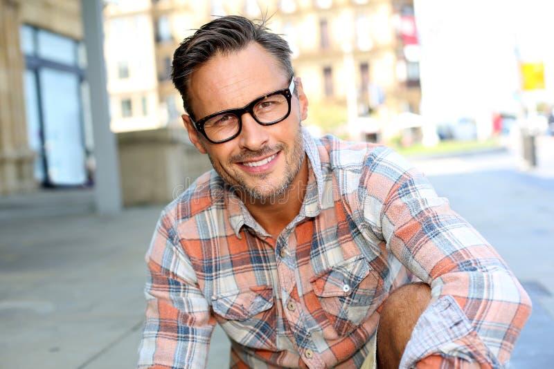 Uomo d'avanguardia con gli occhiali che si siedono nella città immagini stock libere da diritti