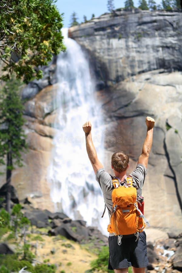 Uomo d'escursione felice che incoraggia nel successo dalla cascata immagine stock