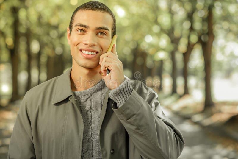 Uomo dai capelli corti sorridente in attrezzatura grigia che parla su un telefono cellulare immagine stock libera da diritti