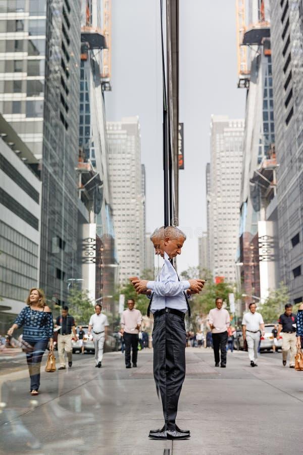 Uomo dai capelli grigi anziano con un telefono cellulare in NYC fotografia stock