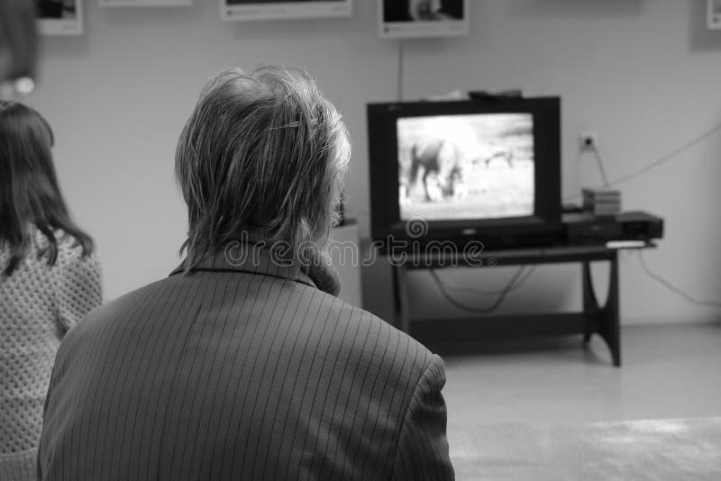 Uomo dai capelli grigi anziano in rivestimento che guarda TV in corridoio del museo provinciale Vista dalla parte posteriore immagine stock libera da diritti