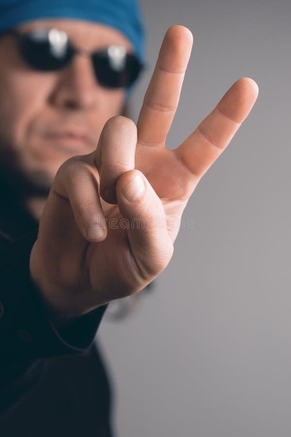 Uomo dai capelli lunghi con gli occhiali da sole che mostrano il segno di pace immagine stock libera da diritti