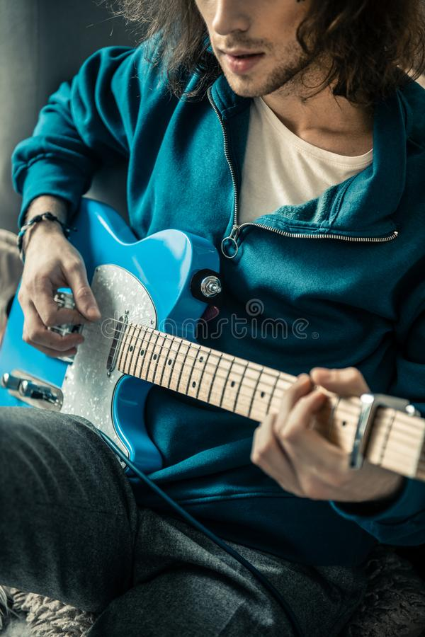Uomo dai capelli lunghi con stoppia nera che porta maglietta felpata blu fotografia stock