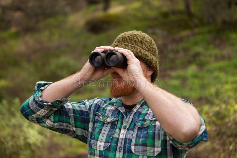 Uomo dai capelli rossi che guarda tiro un binoculare immagine stock
