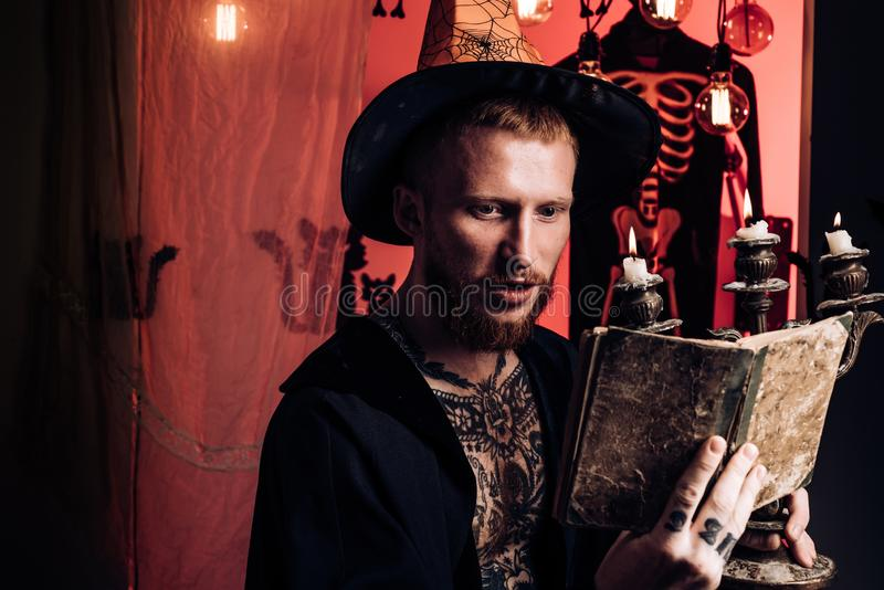 Uomo dai capelli rossi che legge un libro magico con i periodi Padre felice sul fondo di Halloween con il libro del magik Cappell immagini stock libere da diritti