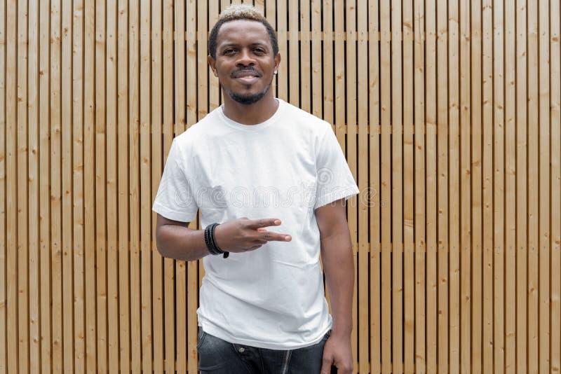 Uomo dalla carnagione scura attraente in maglietta bianca che mostra il segno di vittoria fotografia stock libera da diritti